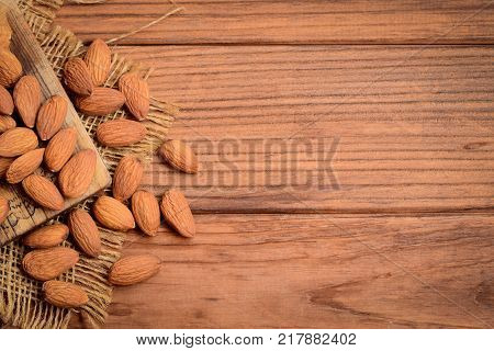 Raw almond nuts on a wooden background with copy space for text. Crunchy brown cased almonds. Good source of protein, fiber, vitamins and nutrients. Top view