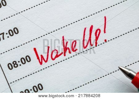 The inscription WAKE UP at 8 a.m. in the planner. Concept of early awake.