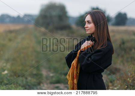 A young woman portrait with village grass road on background. Cloudy autumn weather. Close-up shot