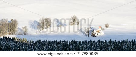 Traditional bavarian chapel in lovely rural countryside on snowy winter sunrise seen from above. Weitnau, Allgau, Bavaria, Germany.