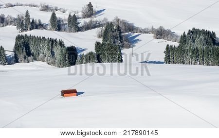 Orange barn building in white snow landscape. Aerial view of rural countryside on snowy winter day. Weitnau, Bavaria, Germany.