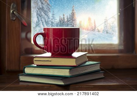Hot tea cup on a frosty winter day window background.