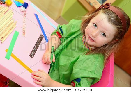 happy smiling kid drawing at home or school kindergarden or kindergarten