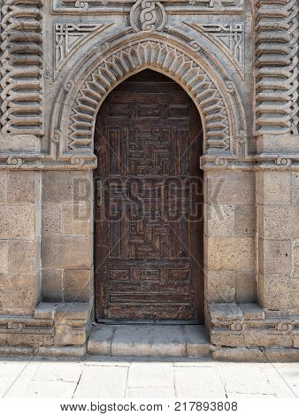 Cairo, Egypt - December 2, 2017: Grunge wooden ornate aged vaulted arched door on exterior decorated stone bricks wall at Manial Palace of prince Mohamed Ali Medieval Cairo
