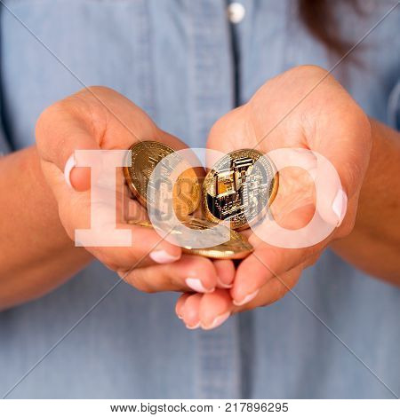 In the photo the girl gives coins as a symbol - Initial coin offering. The ICO procedure picture can be used in publications about the modern economics of the block chain.