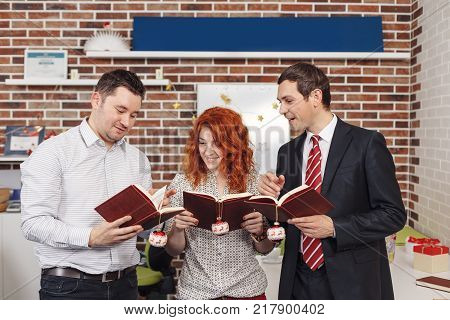 Merry Christmas and New year book lovers. Three people holding books with Christmas decorations in hands smiling while looking on the pages and discussing the subject poster