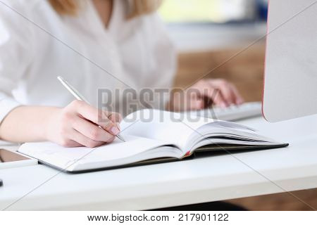 Female hand holding silver pen ready to make note in opened notebook sheet. Businesswoman in suit at workspace make thoughts records at personal organizer white collar conference signature concept