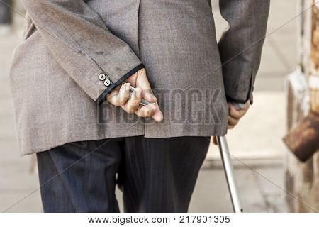 an elderly man walks slowly with a cane and holds in his hand the last money he has. old and old clothes and rags on the back of a tortured man