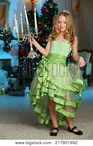 Beautiful charming pretty blond child-girl in a festive green dress with luminous candles on the background of a New Year tree.