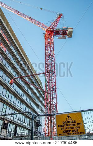 Danger construction site keep out sign with red crane over city office block. Dangerous inner-city building work.