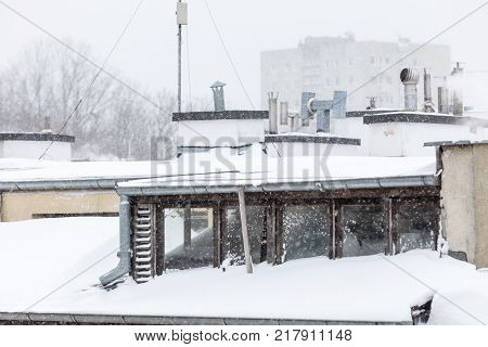 Outdoor shot of cozy room in the attic windows from outside. Building covered with winter snow.