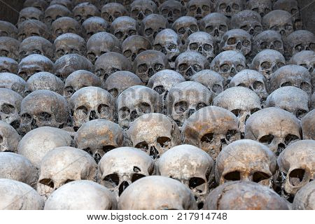 Brno, Czech Republic - August 19, 2017 : Pile of human skulls Brno Ossuary Czech Republic. Concept of death evil terror and genocide. Scary skulls spider web dust in catacombs Human remains in crypt Ancient burial under St James Church