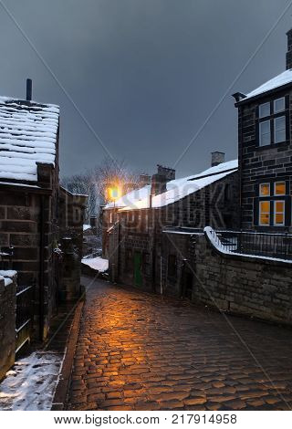 the village of heptonstall in the snow at night with lamps shining onto the cobbled road