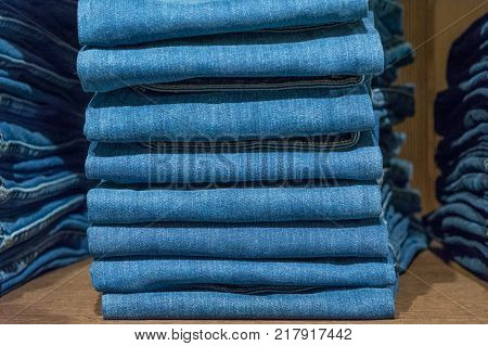 Jeans stacked on a wooden background in store