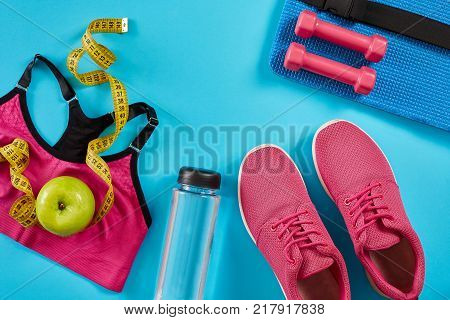 Sneakers with measuring tape on cyan blue background. Centimeter in yellow color, pink sneakers, female sport top and bottle of water, copy space.. Sport shoes and sportive equipment for healthy shape. Sports and healthy lifestyle concept. Still life