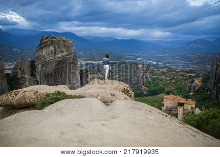 Photographer female  with camera in the white plaid on the edge of the rock look on the monasteries of Meteora. Meteora in Greece in Thessaly at the early morning