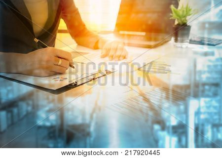 Business Logistics concept Businessman working calculate and re check report cost logistic warehouse with color blue warehouse background