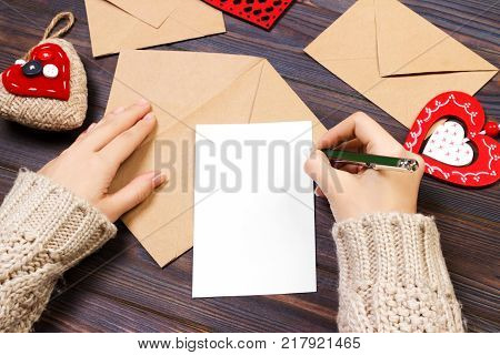 Woman writing love letter or romantic poem for Valentines day top view of female hands. Valentine day concept with copyspace.