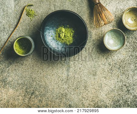Flat-lay of Japanese tools for brewing matcha green tea. Matcha powder in tin can, Chashaku spoon, Chasen bamboo whisk, Chawan bowl and ceremony cups over concrete background, top view, copy space