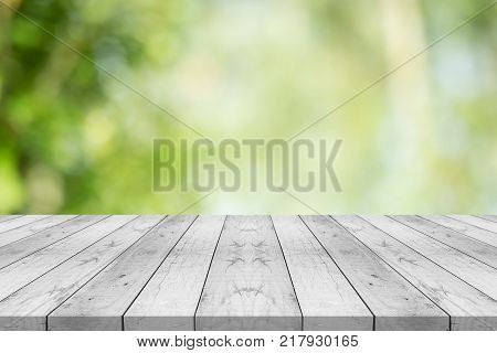 Empty white wood table top on nature green blurred background space for montage show products