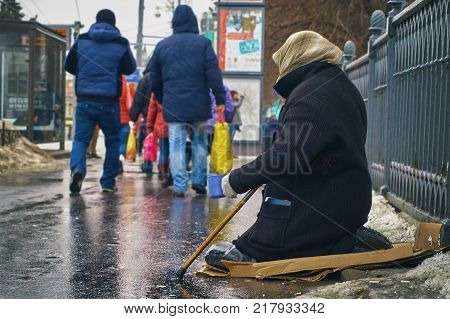 Woman beggar with walking stick and a cup asking for money on Moscow street in winter