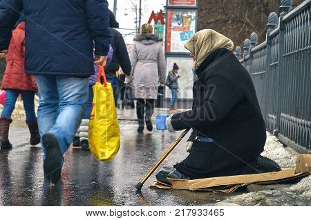 Moscow-January 31, 2016. Beggar with walking stick and a cup asking for money on busy Moscow street in winter