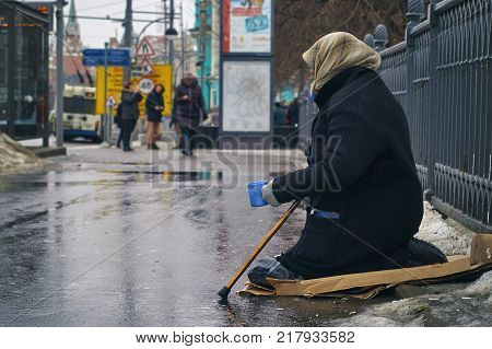 Old female beggar wearing a shabby overcoat asking for money on Moscow street in winter