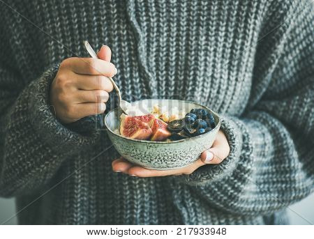 Healthy winter breakfast. Woman in grey woolen sweater eating rice coconut porridge with figs, berries and hazelnuts. Clean eating, vegetarian, vegan, alkiline diet food concept