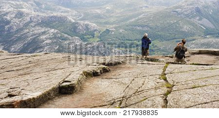 PULPIT ROCK, NORWAY ON JULY 02. View of tourists visit the Pulpit Rock on July 02, 2010 in Lysefjorden, Norway. Strong winds, stand in the center of the cliff. Editorial use.