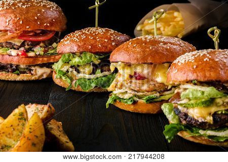 Four homemade hamburgers on wooden table. Buns with sesame seeds, beef burgers and various ingredients. Rustic style. Copy space. Still life hamburger and French fries