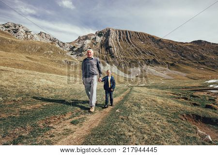 Grandfather with grandson walks on mountain road