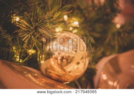 Decoration bulb, green fir tree, golden x-mas toys and lights.