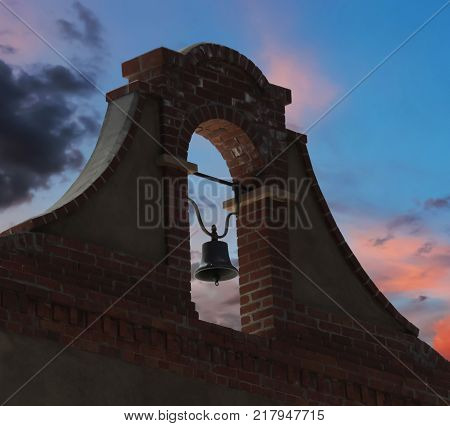 A Brick and Stucco Bell Tower at Twilight in a Sunset Sky