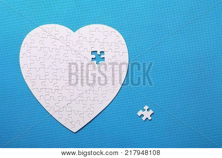 White details of a puzzle on blue background. A puzzle is a puzzle from small pieces. Heart shape of the details. Hands folding puzzle in white.