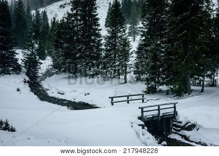 a small river flowing through the snowy landscape under a bridge