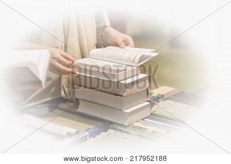 Close-up of woman's hands with a lot of interesting books, bookstore. Education, school, study, reading fiction concept. Light background