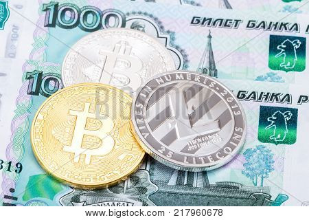 Coins of Cryptocurrency lying on the russian ruble banknotes. Business concept of new virtual money