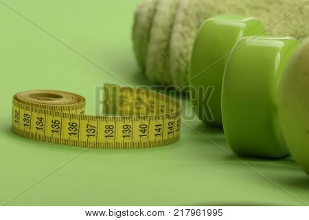 Tape measure in yellow color near lightweight barbells close up. Dumbbells in green color twisted measure tape and towel on green background. Healthy regime equipment. Diet and sport regime concept
