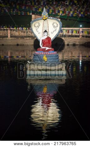 Sculptural composition - Buddha meditating under protection of the king of snakes in the middle of the lake Muchalinda in Bodh Gaya near Mahabodhi Temple where historical Buddha Shakyamuni has reached an enlightenment.