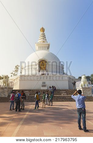 The young resident of India photographs the friends against the background of the Japanese shanti-stupa close to the place where Buddha has made the second turn of a wheel of the teaching. Radzhgir, State of Bihar India on February 1 2014
