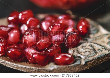 Close up of Pomegranate kernels with rustic spoon