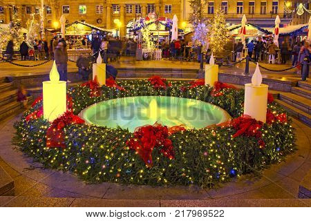 "Mandusevac fountain on Ban Jelacic square decorated with advent wreath as part of ""Advent in Zagreb"" poster"
