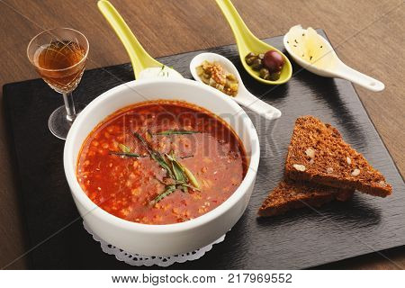 Delicious saltwort with smoked meat, served with rye-bread, assortment of snacks and glass of hard drink. Traditional russian meals in modern restaurant serving