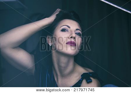 A studio portrait of a beautiful young female model holding her hair up. The photo has a retro/vintage/film look.