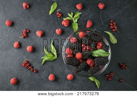 Top view photo on a glass plate with ripe red blackberries raspberries currant and green mint leaves on a black surface. Macro photo of ripe blackberries raspberries and berries of currant.