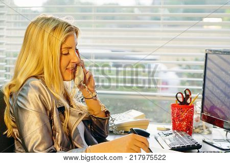 Efficient smiling secretary answering phone calls and talking with customers she is sitting at her desk working.