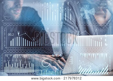 Unrecognizable businessmen using device at workplace with digital business interface. Business and accounting concept. Double exposure