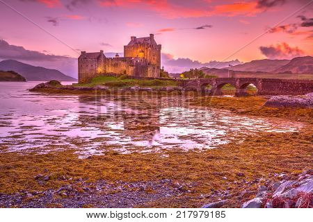 Magenta sunset at Eilean Donan Castle, Dornie, Kyle of Lochalsh in Scotland, United Kingdom. The most visited castle in the UK. Located on an island at the confluence of three sea lochs.