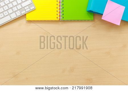 Above View Of Office Workplace With Blank Desk Space. Colorful Paper Book Keyboard Folder And Pink S