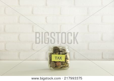 Yellow Tax Label On Saving Money Jar With World Coins White Bricks Background. Taxation Of Social We